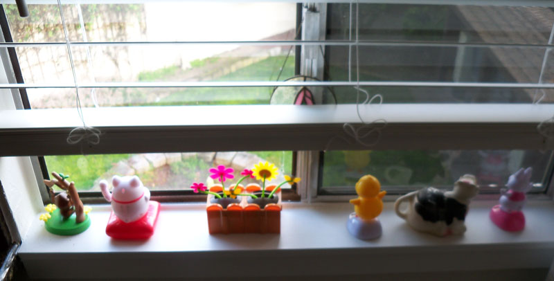 Photo of several toy items in a window sill