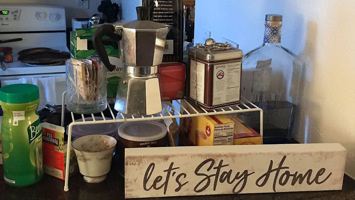 "Sign reading ""Let's Stay Home"" in front of kitchen items"